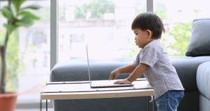 Asiatischer Junge, der im Wohnzimmer spielt stock footage