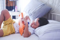Asiatischer Junge, der on-line-Video auf Bett aufpasst lizenzfreies stockbild