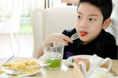 Asiatischer Junge, der Scheibe der Wassermelone isst. Stockbilder
