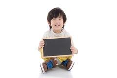 Asiatischer Junge, der schwarzes Brett auf weißem Hintergrund lokalisiert hält Lizenzfreies Stockfoto