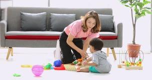 Asiatischer Junge, der Spielwaren mit seiner Mutter spielt stock video footage