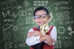Asiatischer Junge, der Trophäe in der Klasse hält Lizenzfreie Stockfotos