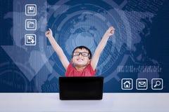 Asiatischer Junge, der unter Verwendung des Laptops auf blauem Hintergrund gewinnt Stockbilder