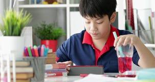 Asiatischer Junge, der zu Hause auf Tablet-Computer trinkt und aufpasst stock video footage