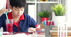 Asiatischer Junge, der zu Hause auf Tablet-Computer trinkt und aufpasst stock footage
