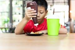 Asiatischer Junge des glücklichen Gesichtes, der Schokolade auf Waffeln zum Frühstück zusammendrückt lizenzfreie stockfotos