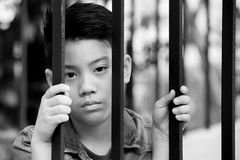 Asiatischer Junge hinter Eisenstangen Stockfotografie