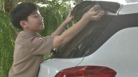 Asiatischer Junge im einheitlichen Auto der Pfadfinder, das sich zu Hause, Thailand-Pfadfinder zu Hause helfen Ihrer Familie wäsc stock footage