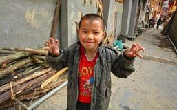 Asiatischer Junge 8 Jahre alt, spielend in der Straße in der chinesischen Landschaft. Lizenzfreies Stockfoto