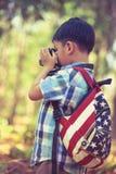 Asiatischer Junge mit Digitalkamera in schönem im Freien Retro- Art Stockfotografie