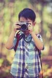 Asiatischer Junge mit Digitalkamera in schönem im Freien Retro- Art Stockfotos