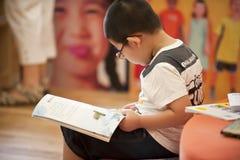 Asiatischer Junge mit Gläsern las Buch Stockfoto
