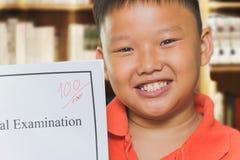 Asiatischer Junge mit Partiturprüfungsblättern Stockbilder