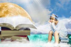 Asiatischer Junge, sitzend auf einem Stapel von Büchern Lizenzfreie Stockfotografie