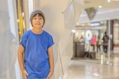 Asiatischer Junge tragende Kleidung einer Hut Abnutzungs-Straße, Lächeln, das glücklich im Mall lächelt Lizenzfreie Stockbilder