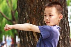 Asiatischer Junge tut Übungen Stockbild