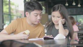 Asiatischer Junge und Mädchen, die mit Karikaturbuch, nettes asiatisches sitzendes Kind Lese, buch am Café mit Lächelngesicht zu  stock video