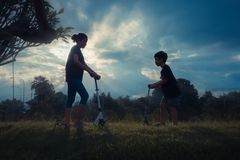 Asiatischer Junge und Mädchen, die Rollerfeld spielt lizenzfreie stockbilder