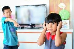 Asiatischer Jungenärger zu einem Mädchen - rasend scherzt Stockfotos