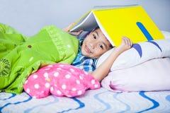 Asiatischer Jungenbedeckungskopf mit Buch und dem Lächeln getrennte alte Bücher Stockfotografie