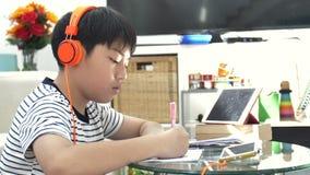 Asiatischer Jungenwarenkopfhörer und auf dem Tisch tun Hausarbeit im Wohnzimmer stock video