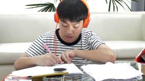Asiatischer Jungenwarenkopfhörer und auf dem Tisch tun Hausarbeit im Wohnzimmer stock video footage