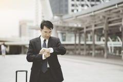 Asiatischer junger Geschäftsmann, der die Zeit überprüft Stockfotos