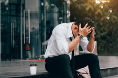 Asiatischer junger Geschäftsmanndruck, der im Front Office mit seinem sitzt lizenzfreie stockfotos
