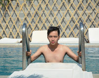 Asiatischer junger Mann, der auf einem Swimmingpool sich entspannt Lizenzfreies Stockbild