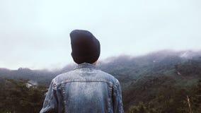 Asiatischer junger Mann in Jean-jecket und in schwarzem Hut, die an der Bergspitze über Wolken und Nebel Wanderer im Freien wande stockfoto