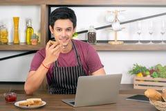 Asiatischer junger Mann mit dem Licht, das Toast isst stockbilder