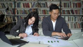 Asiatischer junger Paarmann und weibliche Funktion auf Projekt in der Bibliothek stock video footage