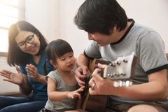 Asiatischer junger Vater, Mutter und Tochter, die das Gitarre toget spielt lizenzfreie stockfotos