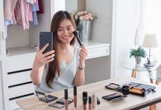 Asiatischer junger weiblicher Blogger notierender vlog Videogebrauch beweglich mit lizenzfreie stockfotos