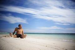 Asiatischer Kerl, der auf dem Strand sich entspannt Stockfoto