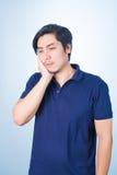 Asiatischer Kerl, der die Zahnschmerzen hält sein Gesicht mit seiner Hand hat, lizenzfreies stockfoto