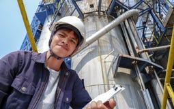 Asiatischer Kerl, der eine Sturzhelm Funktion in einer großen industriellen Fabrik überprüft das Produktionsverfahren trägt lizenzfreie stockfotografie