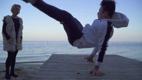 Asiatischer Kerl in der zufälligen Kleidung, die Breakdance vor seiner schönen kaukasischen Freundin nahe dem See tanzt nett stock footage