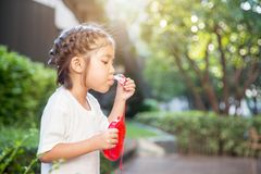Asiatischer Kinderfokus auf dem Spielen der Blase auf Park stockfotos