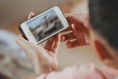 Asiatischer Kinderjungenholding- und -touch Screen von Smartphone stockfotos