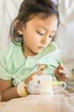 Asiatischer Kinderkrankenhauspatient, der mit Infusion niedergedrückt glaubt Stockfoto