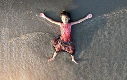 Asiatischer Kindernehmenrest auf Sandstrand als Freiheit stockbilder