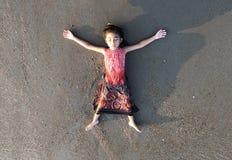 Asiatischer Kindernehmenrest auf Sandstrand als Freiheit lizenzfreies stockfoto