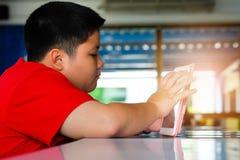 Asiatischer Kindjunge sind süchtig machend, Tablette spielend lizenzfreie stockfotos