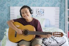 Asiatischer kleiner Junge, der übt, um Akustikgitarre zu spielen Stockfotografie