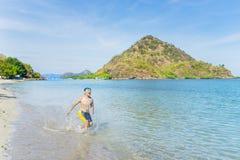 Asiatischer kleiner Junge, der im rosa Strand spielt Stockfoto