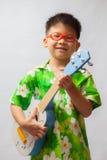 Asiatischer kleiner Junge, der Ukulele spielt Stockbild