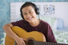 Asiatischer kleiner Junge mit Kopfhörer und Gitarre Lizenzfreie Stockfotografie