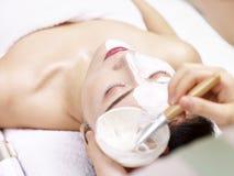 Asiatischer Kosmetiker, der Gesichtsmaske auf Gesicht der jungen Frau anwendet Lizenzfreie Stockfotos