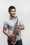 Asiatischer Kursteilnehmer, der ein Saxophon anhält Lizenzfreie Stockfotos